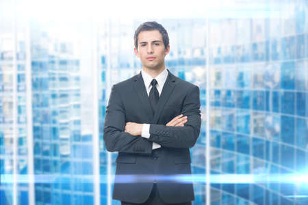 success man: Portrait of business man with crossed hands, isolated on blue background. Concept of leadership and success