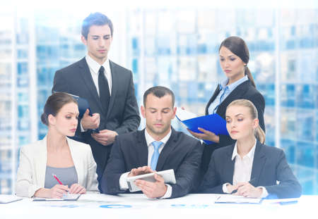 Group of executives discussing while sitting at the table, blue background. Concept of teamwork and cooperation photo