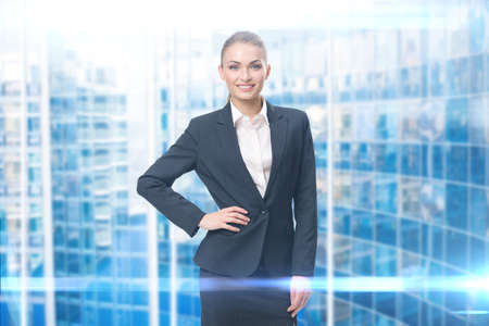 Portrait of businesswoman with her hand on hip, blue background. Concept of leadership and success Standard-Bild