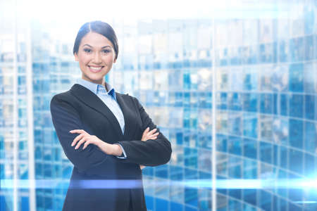 Portrait of female executive with hands crossed, blue background. Concept of leadership and success photo