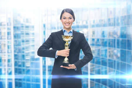 Portrait of businesswoman with golden cup, blue background. Concept of win and success Standard-Bild