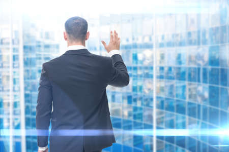 Backview of businessman waving hand, blue background