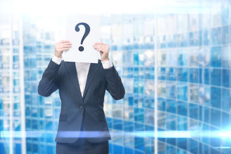 Businesswoman handing question mark in front of her face, blue background. Concept of problem and solution photo