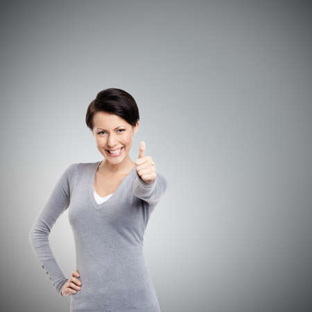 Pretty girl gives thumb up, isolated on grey