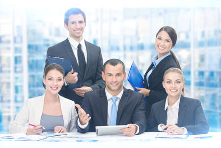 Group of business people working while sitting at the table, blue background. Concept of teamwork and cooperation