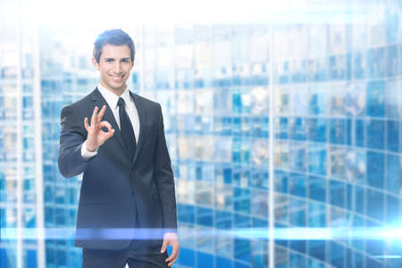 Portrait of ok gesturing businessman,è èlue background. Concept of leadership and success Standard-Bild