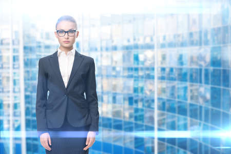 Half-length portrait of businesswoman wearing glasses with black frame, blue background. Concept of leadership and success photo