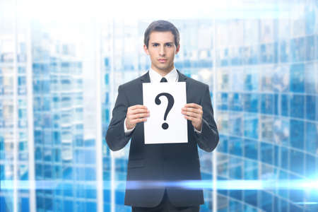 Portrait of business man handing question mark, blue background. Concept of problem and solution photo