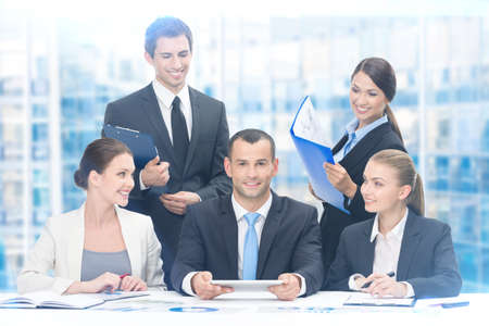 Group of executives debating while sitting at the table, blue background. Concept of teamwork and cooperation photo