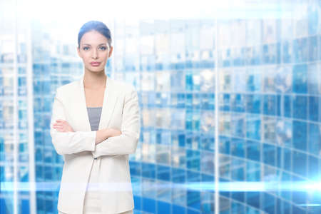 Half-length portrait of businesswoman with arms crossed, blue background. Concept of leadership and success photo