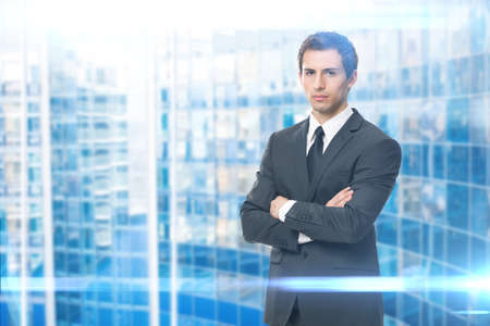 Portrait of serious businessman with crossed hands, blue background. Concept of leadership and success photo