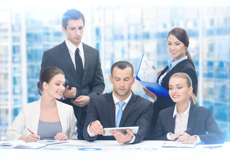 young executive: Group of executives discussing while sitting at the table, blue background. Concept of teamwork and cooperation