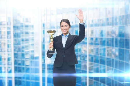 Portrait of businesswoman with cup, blue background. Concept of win and success photo