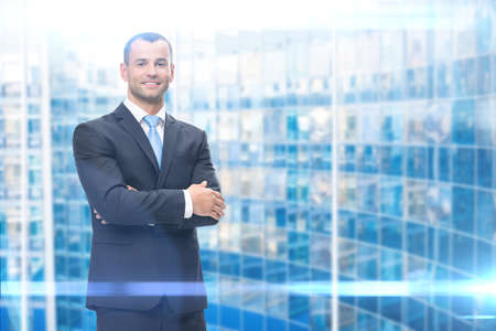 Portrait of business man with hands crossed, blue background. Concept of leadership and success Standard-Bild