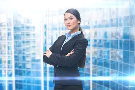 blue shirt: Portrait of businesswoman with hands crossed, blue background. Concept of leadership and success Stock Photo