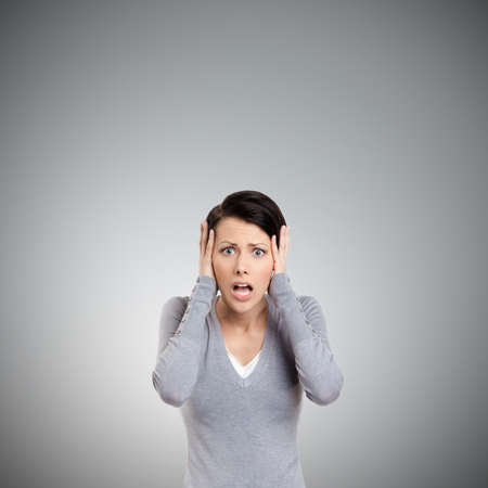 Confused woman puts her hands on the head, isolated on grey Standard-Bild