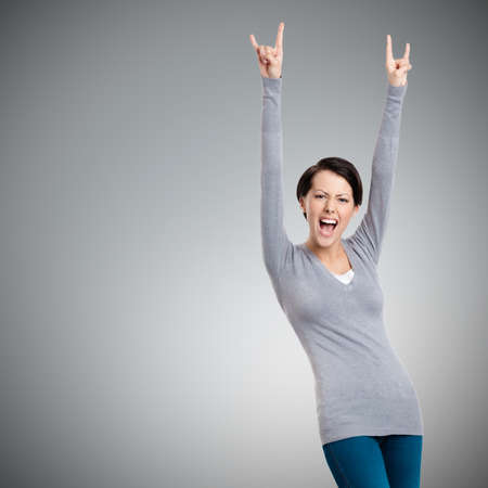 Glad pretty woman puts her hands up, isolated on grey photo