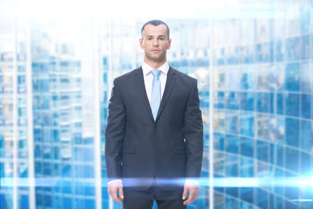 Portrait of serious business man, on blue background