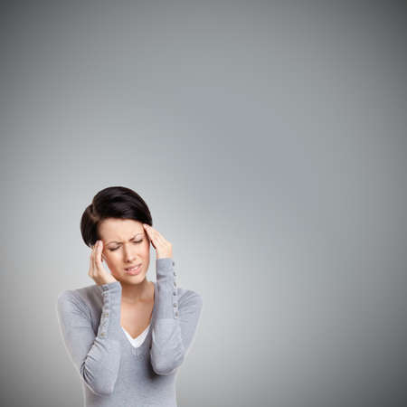 put pressure: Girl has a headache, isolated on grey Stock Photo