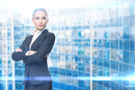 Portrait of businesswoman with hands crossed, on blue background. Concept of leadership and success Standard-Bild