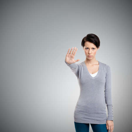 Smart girl shows stop gesture, isolated on grey background Standard-Bild