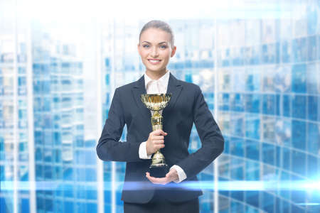 Portrait of businesswoman keeping golden cup, blue backround. Concept of victory and success