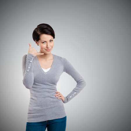 Smiling girl makes a phone call gesture, isolated on white
