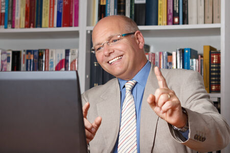 Happy old man celebrating in front of his computer