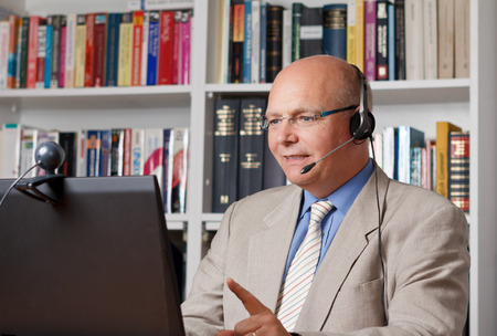 Friendly businessman with headphones in front of a computer with camera Standard-Bild