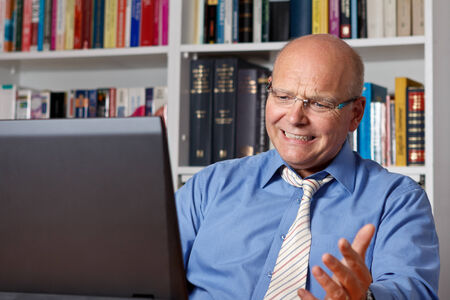 Aged man sitting very frustrated and stressed in front of his notebook photo