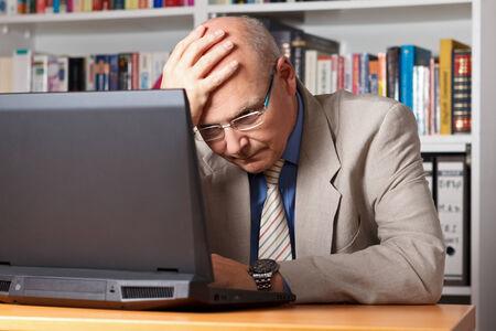 Gestrest en gefrustreerd oudere man in de voorkant van zijn laptop