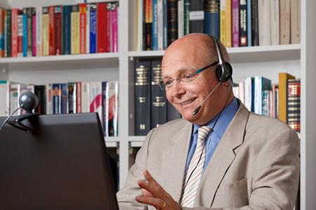 tutor: Feliz y riendo el hombre que llama por teléfono a través de Internet
