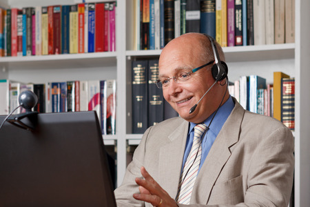 tutoring: Happy and laughing man telephoning via the internet Stock Photo
