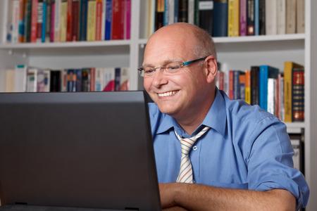 Ontspannen bejaarde zakenman lachen in de voorkant van zijn laptop, copyspace