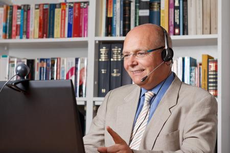 Lachende hogere empoyee telefoneren met behulp van de computer, webcam und headset