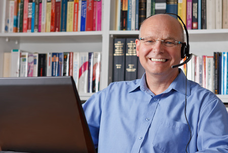 Elderly man with headphones and computer laughing happily, copyspace photo