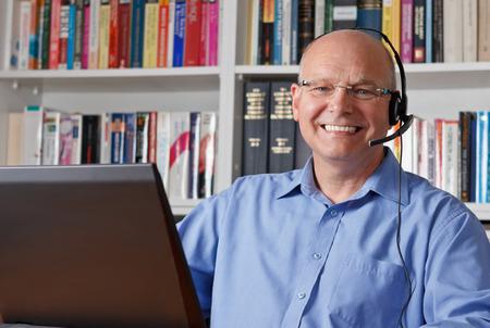 Oudere man met een koptelefoon en computer lachen gelukkig, copyspace Stockfoto