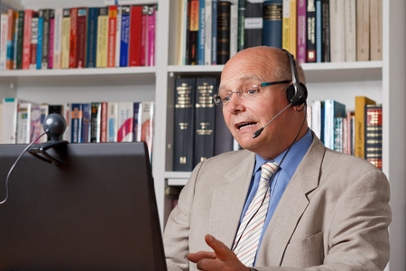 Lecturer at an online workshop with computer, camera and headset Standard-Bild