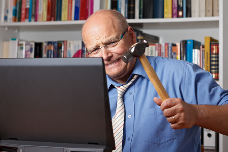 Furious man with bald patch hitting his computer with a hammer photo