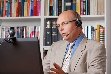 Man in home office talking with colleague