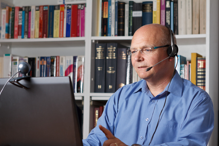 Man telephoning with computer, headset and webcam, copyspace