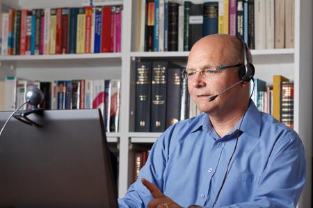 Man telefoneren met computer, headset en webcam, copyspace