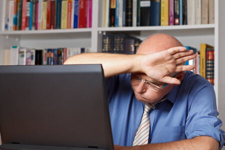 relieved: Old man in front of his computer wiping his brow in relief