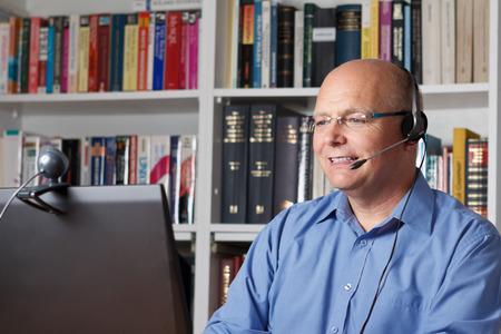 Glimlachend senior man contact opneemt met zijn familie via internet, copyspace Stockfoto