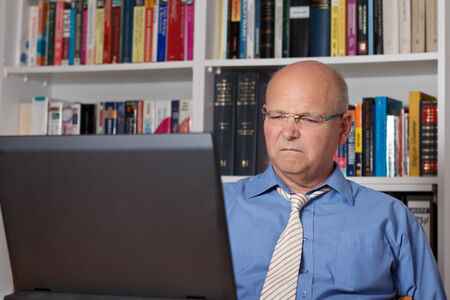 disgusted: Senior man sitting disgusted in front of his computer, copyspace