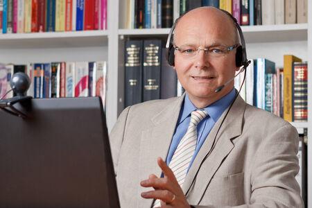 Glimlachend bejaarde zakenman met computer, webcam en een headset