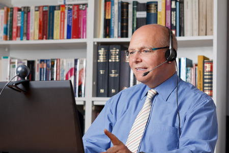 Vriendelijk lachende man met een koptelefoon, laptop en webcam telefoneren