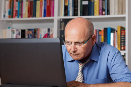 Stressed elderly man staring concentrated on his notebook photo