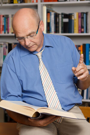 Teacher in library reading aloud out of a book