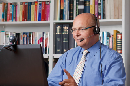 Friendly tutor talking with a student via headphones and internet Banque d'images